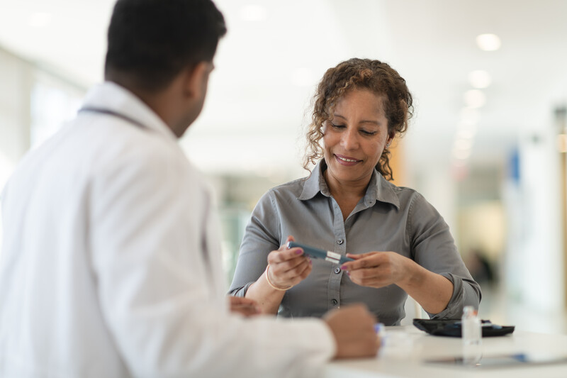 A male Indian doctor meets with a female patient. The woman is a mature adult of African descent. The two people are seated at a table. The patient is diabetic and is holding an insulin pen. The doctor is explaining how to use the device.
