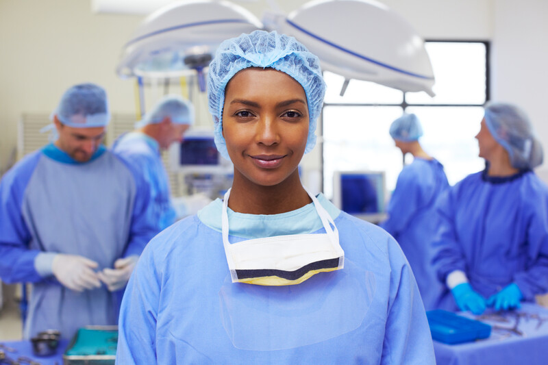 Portrait of an attractive ethnic nurse standing in a busy operating room