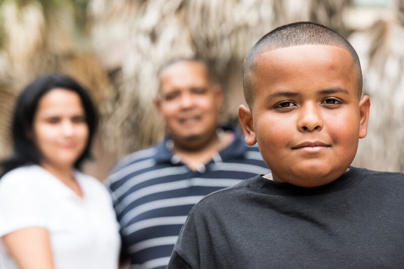 Hispanic child posing smiling with his parents in the background